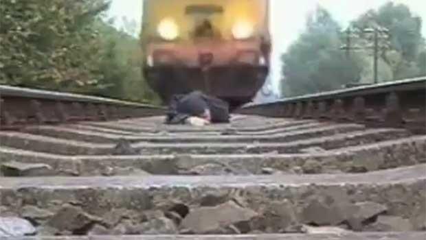Homem escapou ileso após deitar nos trilhos enquanto trem passava. (Foto: Reprodução)