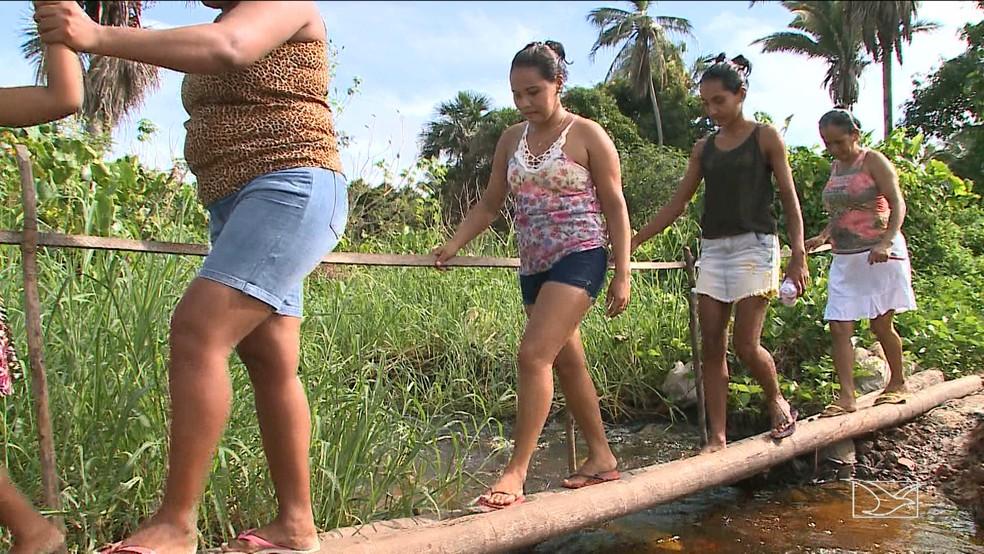 Moradores se arriscam em ponte improvisada no Iguaíba (Foto: Reprodução TV Mirante)