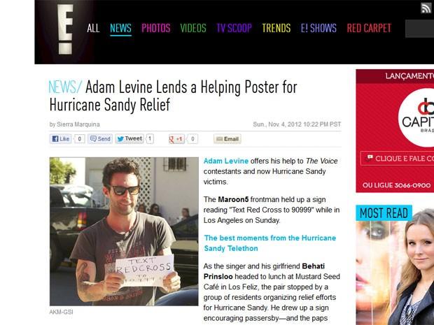 Adam Levine, do Maroon 5, mostra cartaz que escreveu para fotógrafo em Los Angeles; na mensagem, escrita à mão, ele pede doações para a Cruz Vermelha em favor das vítimas do furacão Sandy (Foto: Reprodução/E! Online)