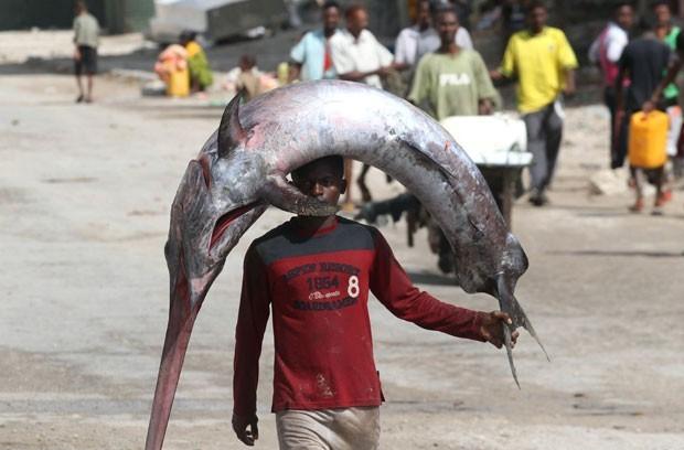 Em foto de 18 de dezembro de 2012, pescador é fotografado carregando um peixe-espada sobre a cabeça em uma rua de Mogadíscio (Foto:  Ismail Taxta/Reuters)