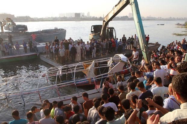 Parentes de passageiros e outras pessoas são vistas enquanto destroços de barco envolvido em acidente no Nilo são retirados do rio nesta quinta-feira (23) no Cairo (Foto: STR/AFP)