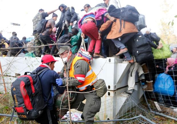 Soldado austríaco tenta conter imigrante que tentava atravessar a fronteira para o país vindo da Eslovênia nesta sexta-feira (30) (Foto: Srdjan Zivulovic/Reuters)