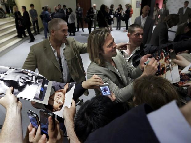 Ator americano Brad Pitt distribui autógrafos em chegada ao Festival de Cannes nesta terça-feira (22) (Foto: Eric Gaillard/Reuters)