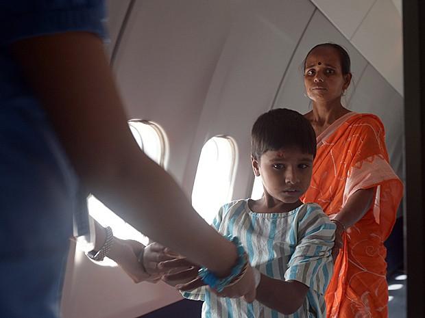 Junto com a mãe, menino indiano chega assustado para cirurgia (Foto: Dibyangshu Sarkar/AFP)