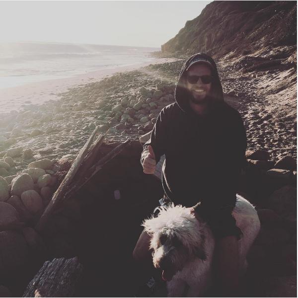 Liam Hemsworth sentado nas costas da cachorrinha Dora (Foto: Instagram)