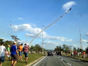 Adolescentes andam em canteiro central de avenida com pedaço de galho e obrigam motoristas parar para pegar pipa (Foto: Mayara Corrêa / G1)