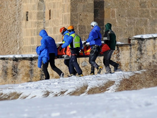 Homens da equipe de resgate carregam o corpo de um dos esquiadores mortos nos Alpes (Foto: Jean-Perre Clatot/AFP)