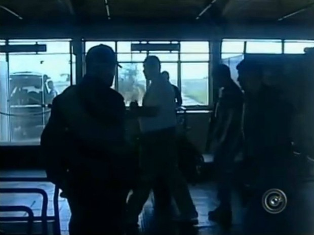 Equipe da TV Tem flagra o momento em que o preso (de camiseta branca e mãos algemadas) deixa o saguão do aeroporto para embarcar para Rondônia. (Foto: Reprodução TV Tem)