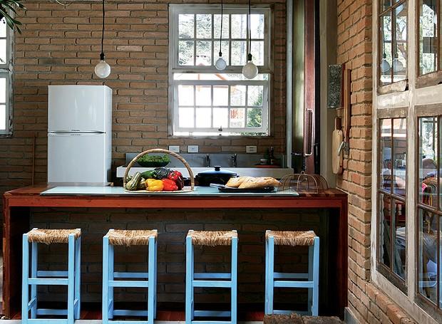 A cozinha segue o estilo simples da casa de campo da arquiteta Evelin Sayar. A iluminação é feita por lâmpadas penduradas e as banquetas de fibra dão um toque de cor (Foto: Marcos Antonio/Casa e Jardim)