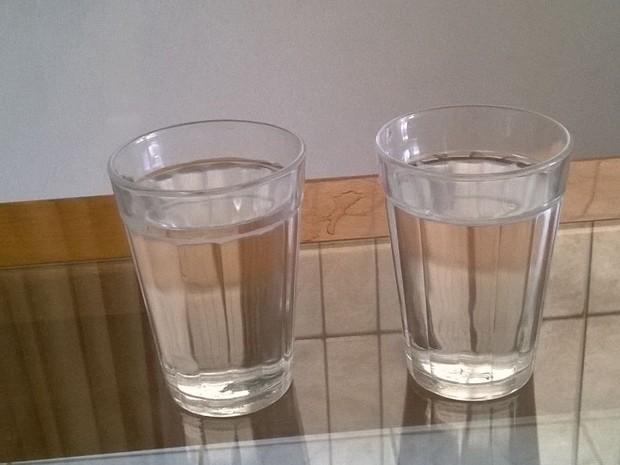 Moradora comparou água mineral (esquerda) e água que chega das torneiras (direita); as duas com a mesma coloração (Foto: Vania de Oliveira/ VC no ESTV)