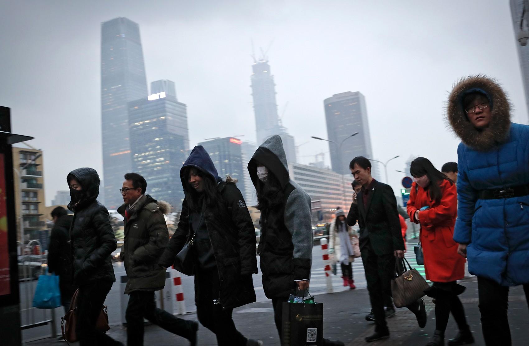Foto de 21 de fevereiro de 2017 mostra moradores de Pequim caminhando em direção a uma estação de metrô, sob céu cinzento de poluição