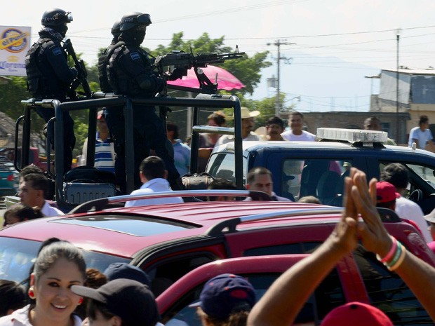 Pessoas cercam um comboio da Polícia Federal a caminho da comunidade de Apatzingan, no Estado de Michoacán, no México. (Foto: Alfredo Estrella/AFP)