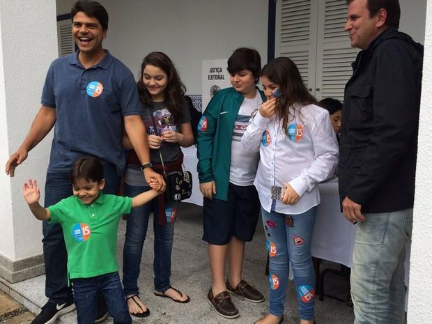 Prefeito Eduardo Paes e o candidato Pedro Paulo com os filhos na seção 167 (Foto: Alba Valéria Mendonça / G1 Rio)
