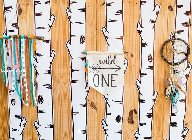 Painel de madeira com troncos de árvore desenhados, flâmulas e filtro dos sonhos com detalhes em laranja e azul turquesa compõem o clima de festa na floresta  (Foto: Divulgação / Lilian Cruz)