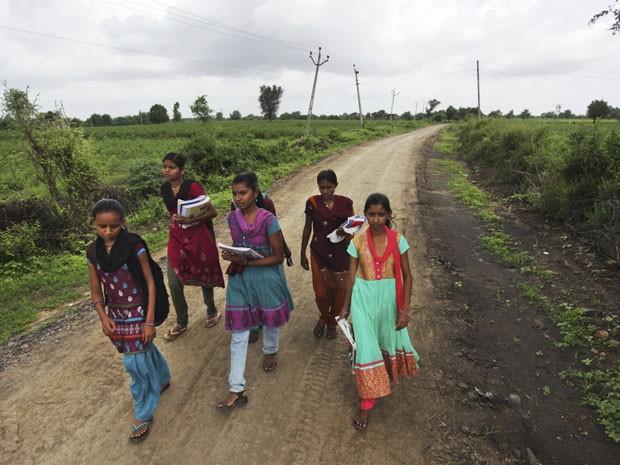 Depois de passarem pelo rio, alunas caminham mais 5 km (Foto: Ajit Solanki/AP)