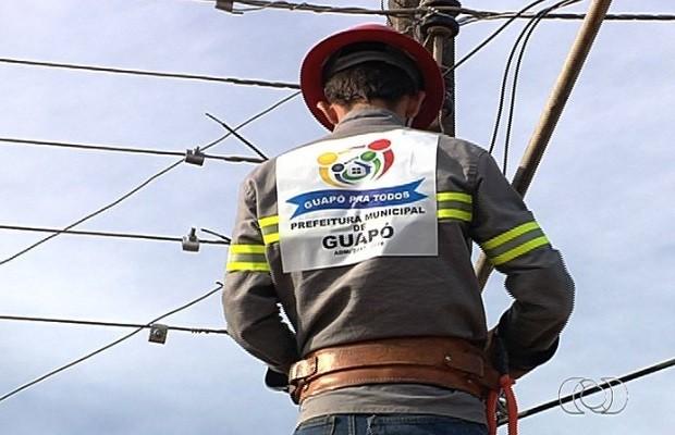 Funcionário  religa energia do prédio da prefeitura de Guapó, em Goiás (Foto: Reprodução/ TV Anhanguera)