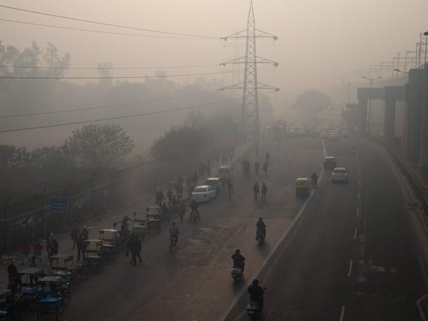 Fumaça e poluição são vistas durante o amanhecer em Nova Deli, na Índia. Uma experiência de duas semanas para combater a poluição na cidade vai limitar o trânsito de veículos, em dias alternados, dependendo se suas placas terminam em par ou ímpar (Foto: Tsering Topgyal/AP)