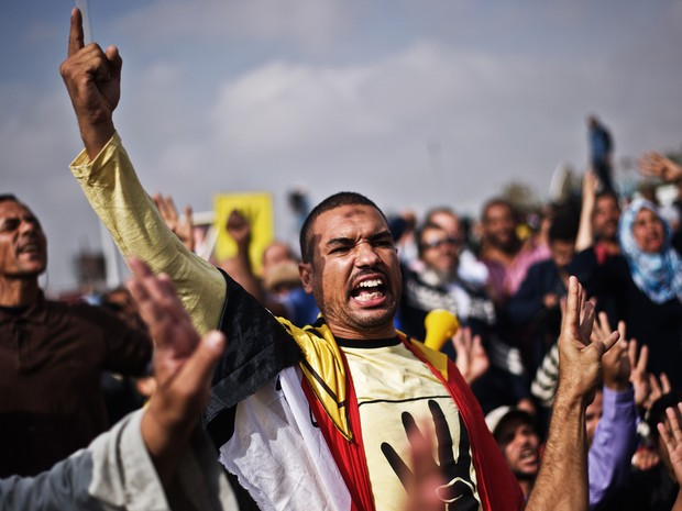 Apoiadores do presidente deposto Mohammed Morsi gritam do lado de fora da Academia de Polícia antes de seu julgamento no Cairo. (Foto: Gianluigi Guercia/AFP)
