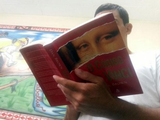 O detento Bruno Leon Gomes Lima com um dos livros que pretende ler – O código Da Vinci, de Dan Brown (Foto: Raquel Morais/G1)