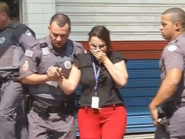Refém é retirada da loja após suspeito se render (Foto: Reprodução / TV TEM)
