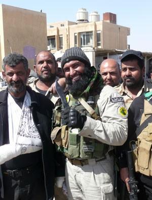 """O miliciano xiita Abu Azrael, cujo nome significa """"Pai do Anjo da Morte"""", posa ao centro com soldados xiitas perto de Tikrit no dia 14 de março (Foto: W.G. DUNLOP/AFP)"""