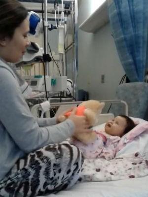 Mãe diverte Sofia com um ursinho de pelúcia (Foto: Reprodução/ Campanha Ajude a Sofia)