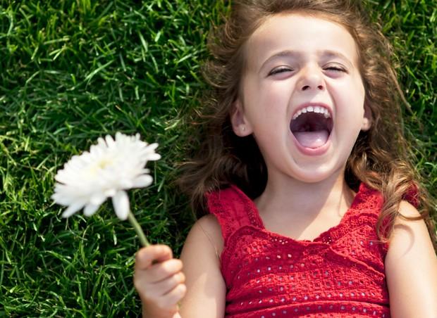 menina; grama; sorriso; flor; feliz; felicidade (Foto: Thinkstock)