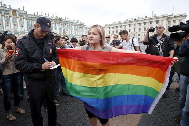Ativista gay posa com bandeira ao ser abordada por policial durante protesto em São Petersburgo neste domingo (2) (Foto: Maxim Zmeyev/Reuters)