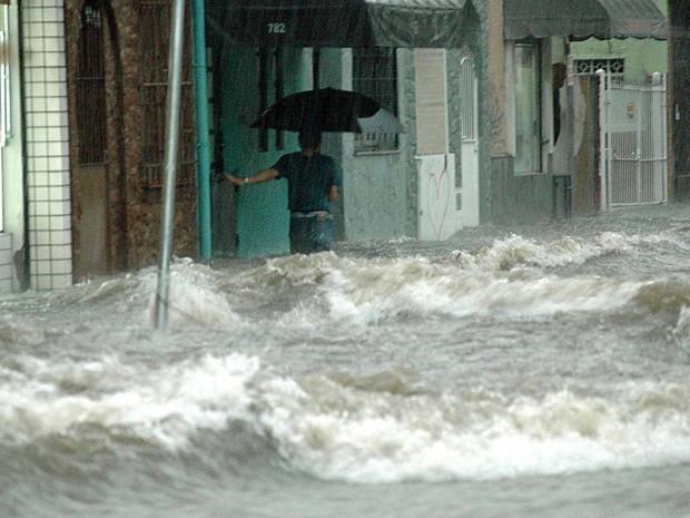 Homem enfrenta ondas durante enchente na zona oeste de SP (Foto: Paulo Preto/Futura Press)