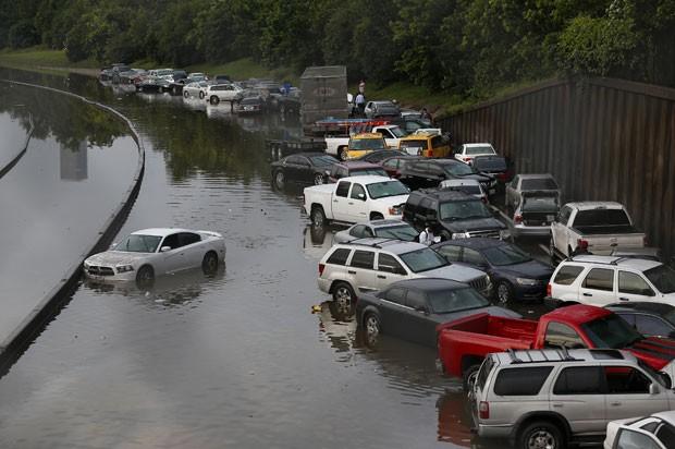 Carros são vistos abandonados após água inundar rodovia em Houston, no Texas, nesta terça-feira (26) (Foto: AARON M. SPRECHER/AFP)
