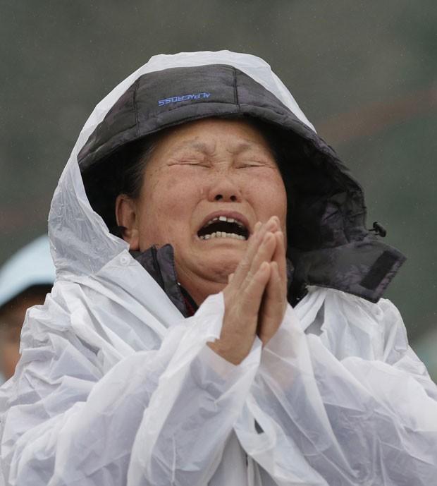 Mulher chora enquanto faz oração por familiar desaparecido, no porto de Jindo, na Coreia do Sul (Foto: Lee Jin-man/AP)