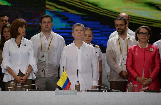Presidente colombiano Juan Manuel Santos e secretária-geral da cúpula Íbero-Americana Rebeca Grynspan, de vestido vermelho, no XXV Encontro Íbero-Americano em Cartagena, na Colômbia.  (Foto: Raul Arboleda/France Presse)