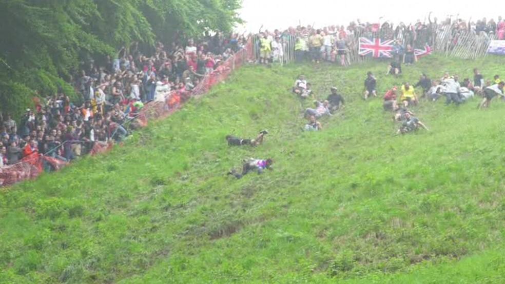 """Todos os anos, milhares de pessoas assistem à tradicional """"corrida do queijo"""" na colina de Copper's Hill, em Gloucestershire, no interior da Inglaterra. (Foto: BBC)"""