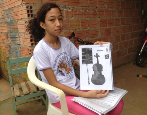 Na apostila das aulas de música, Charliane mostra o violino, o instrumento que gostaria de ganhar. (Foto: Vanessa Vasconcelos/G1)