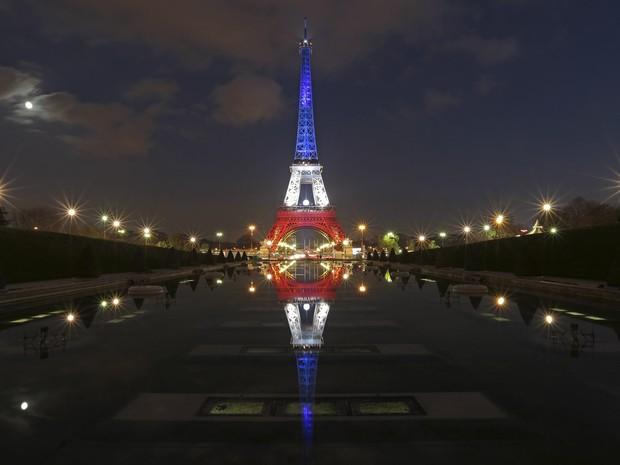 A Torre Eiffel é iluminada com as cores francesas em homenagem às vítimas dos ataques terroristas de 13 de novembro em Paris, na França (Foto: Christian Hartmann/Reuters)
