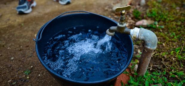 Um morador de São José dos Campos enche um balde com água (Foto: Lucas Lacaz Ruiz/Folhapress)