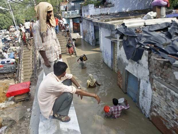 Moradores carregam pertences através de um beco inundado após a cheia do Rio Yamuna, em Nova Délhi. (Foto: Anindito Mukherjee / Reuters)