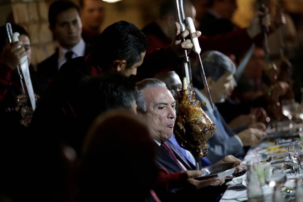 O presidente Michel Temer come carne de churrasco acompanhado de embaixadores de países que importam carne brasileira em uma churrascaria de Brasília, na noite de domingo (19) (Foto: Ueslei Marcelino/Reuters)