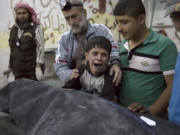 Menino sírio chora em desespero diante do caixão de um familiar e é amparado durante funeral de uma vítima de bombardeio no bairro de al-Soukour, controlado por rebeldes contrários ao governo de Bashar al-Assad, em Aleppo (Foto: Karam al-Masri/AFP)