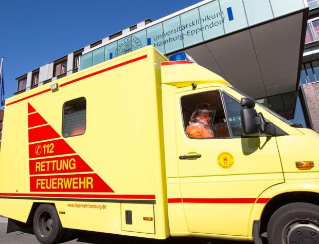 Pessoa em roupa especial é vista em ambulância na entrada do hospital Eppendorf, em Hamburgo, na Alemanha, nesta quarta-feira (27), enquanto levava um médico infectado pelo ebola em Serra Leoa para tratamento no local (Foto: dpa,Georg Wendt/AP)