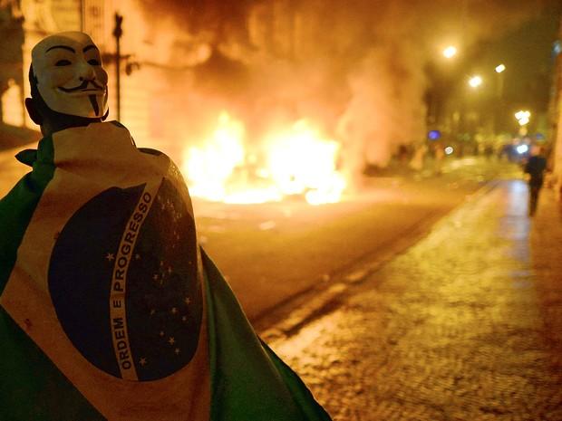 Manifestante mascarado e enrolado em bandeira do Brasil participa de protesto no Centro do Rio (Foto:  Christophe Simon/AFP)