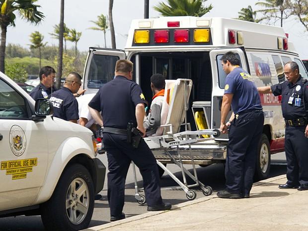 Adolescente que viajou da Califórnia ao Havaí junto com a roda de avião é levado a ambulência no aeroporto de Kahului, em Maui (Foto: AP Photo/The Maui News, Chris Sugidono)