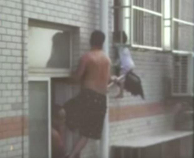 Um chinês usou um esfregão para salvar uma menina que estava pendurada do lado de fora de uma janela no quarto andar de um prédio na cidade de Weifang, na China (Foto: Reprodução/YouTube/CCTV News)