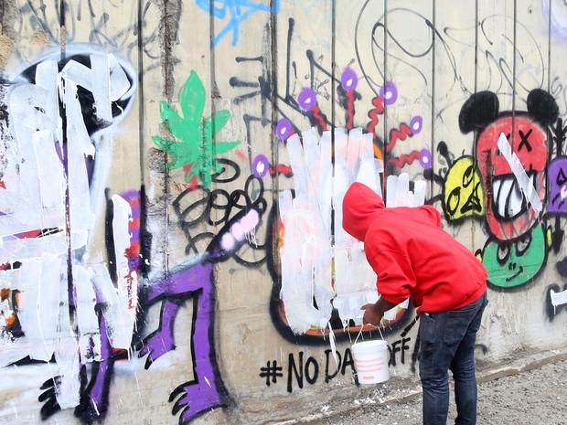 Fotógrafo passa tinta branca em grafite feito por Justin Bieber (Foto: Xande Nolasco / Estadão Conteúdo)