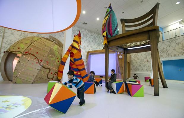 Crianças brincam em setor de recuperação pediátrica do Royal London Hospital, em Londres, na Grã-Bretanha. Chamado de 'Ann Riches Healing Space', o local foi inaugurado na semana passada, em 14 de fevereiro, e foi inspirado na famosa obra 'Alice no País das Maravilhas' (Foto: Neil Hall/Reuters)