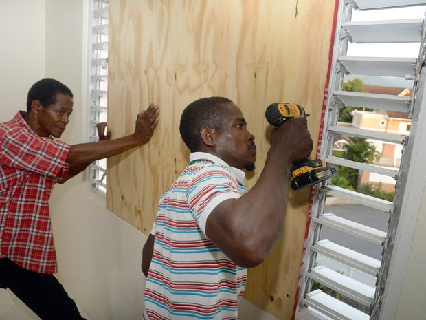 Homem instala placa para proteger a vitrine de uma loja em Kingston. (Foto: AP)