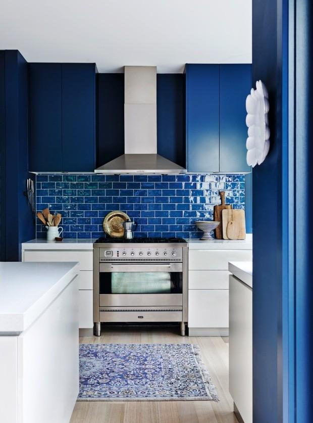 Cozinha. Os azulejos que formam o frontão são da cor Azul Zafiro, mesmo tom usado nos armários. As bancadas brancas e o tapete acrescentam um ar de sofisticação (Foto: Lisa Cohen / Living Inside)
