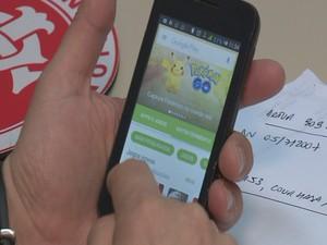 Delegado mostra aplicativo disponível na loja online do celular, mas app não estava instalado (Foto: Reprodução/RBS TV)