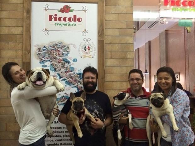 Donos posam com cães na entrada de restaurante de Brasília que oferece petiscos e cerveja própria para pets (Foto: Piccolo Emporium/Divulgação)