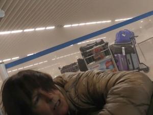 Mulher deita no chão ao lado de bagagens após explosão no Aeroporto de Bruxelas (Foto: Ralph Usbeck/AP)